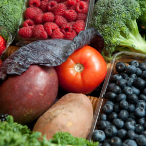 Several fruits and vegetables including raspberries, a tomato, potato, blueberries and broccoli.